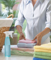 Woman Folding Freshly Washed Towels --- Image by © Royalty-Free/Corbis