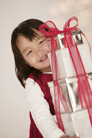 Girl Carrying Christmas Gifts --- Image by © Royalty-Free/Corbis