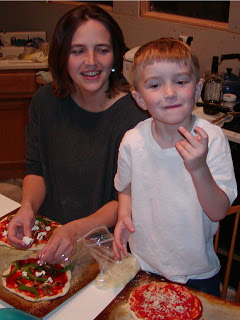 A boy making pizza with his mom