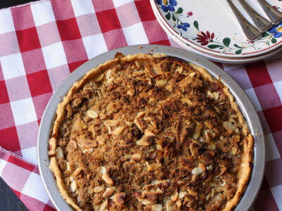 apple pie on checked cloth with plates and forks
