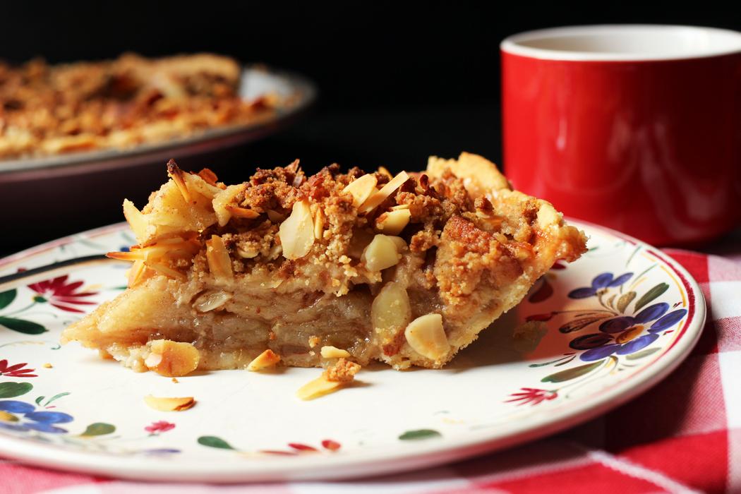 slice of apple pie on plate with mug
