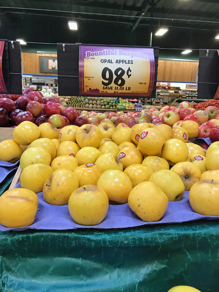 stacks of opal apples on sale at grocery store for 98 cents per pound