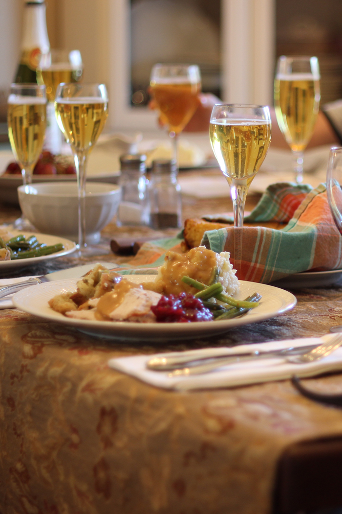 Thanksgiving table set with plates of food and glasses of cider