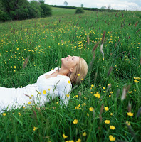 Blond woman lying in field --- Image by © Royalty-Free/Corbis
