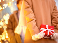 Woman Holding Gift --- Image by © Royalty-Free/Corbis