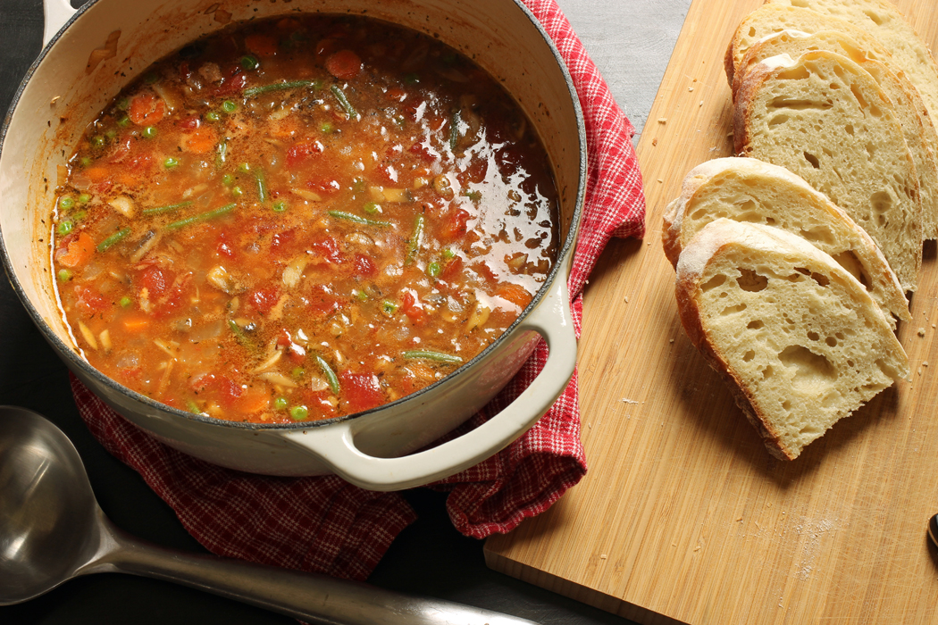 pot of tomato based soup with slices of bread on cutting board
