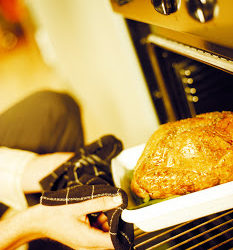 Man taking a goose out of the oven --- Image by © Royalty-Free/Corbis