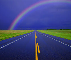 Country road on rainy day with rainbow