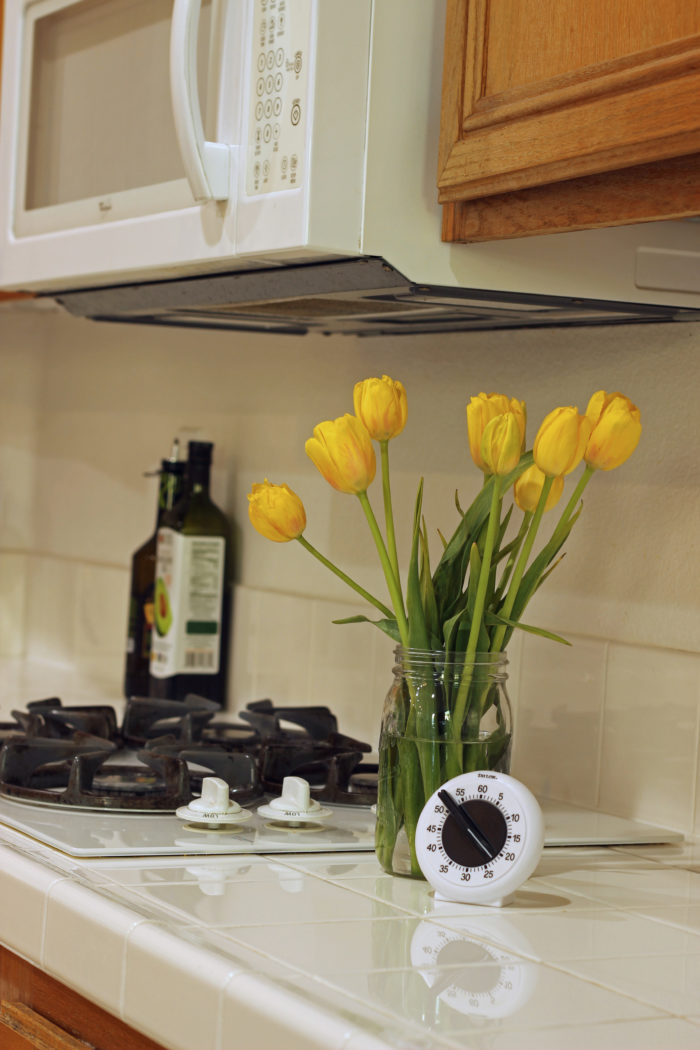 kitchen timer next to vase of yellow tulips by stove