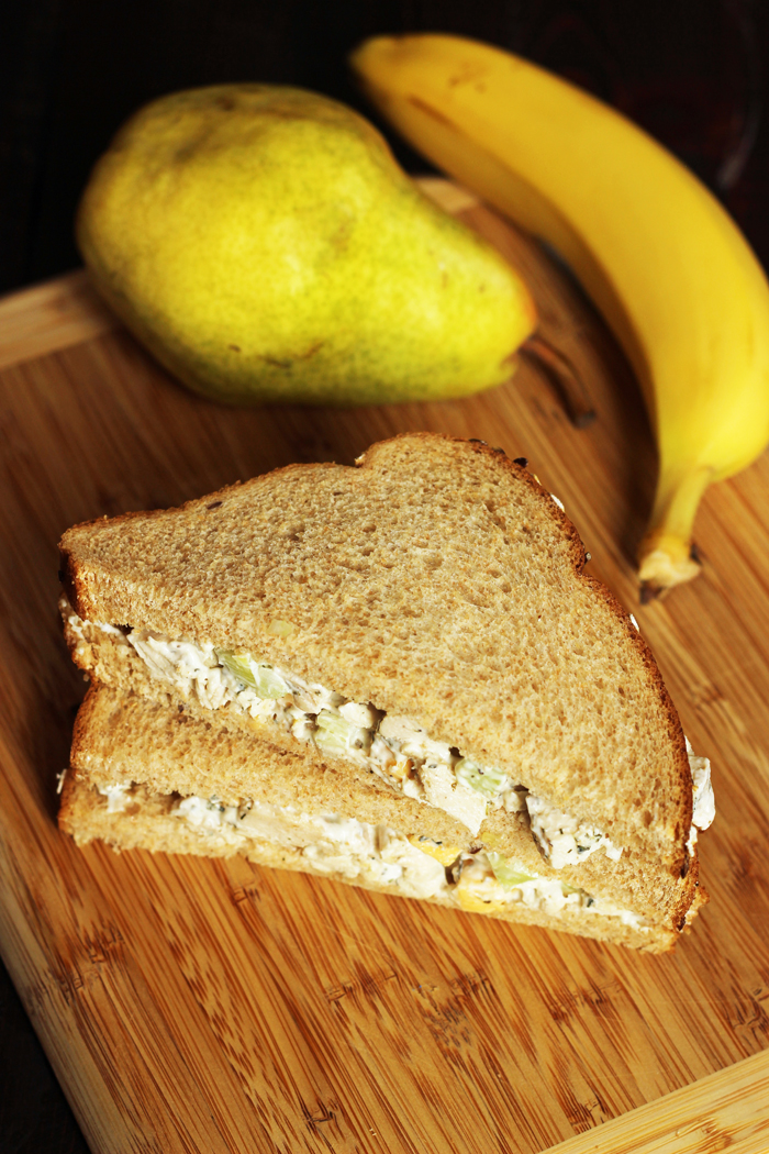 A banana sitting on top of a wooden cutting board, with Sandwich and pear