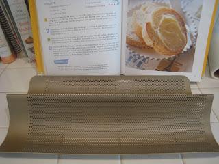 open cookbook next to baguette pan