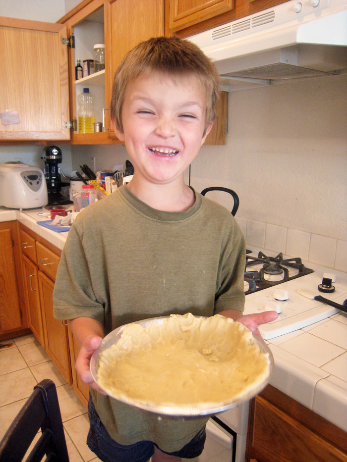 preschool boy holding pie crust he made himself