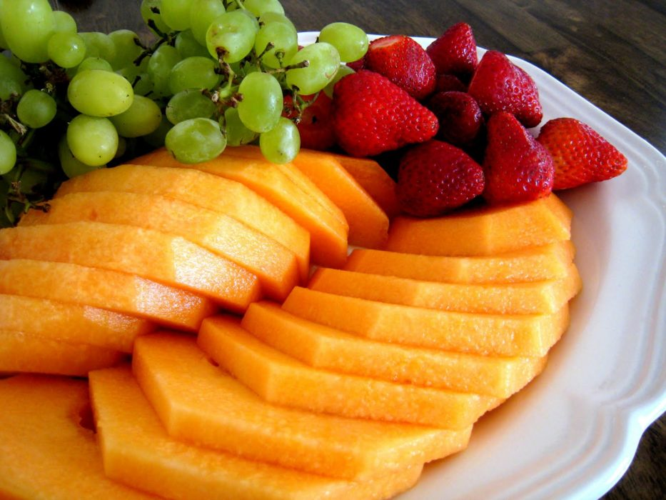 a plate of fruit with sliced melon, berries, and grapes