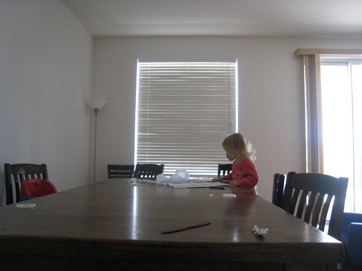 toddler girl sitting at messy table
