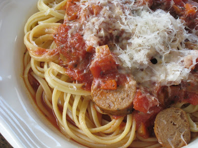 A close up of pasta with sausage and sauce