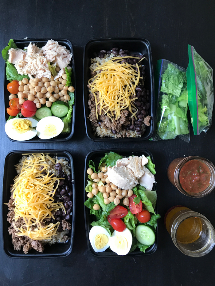 four black lunch boxes with different meals packed in them