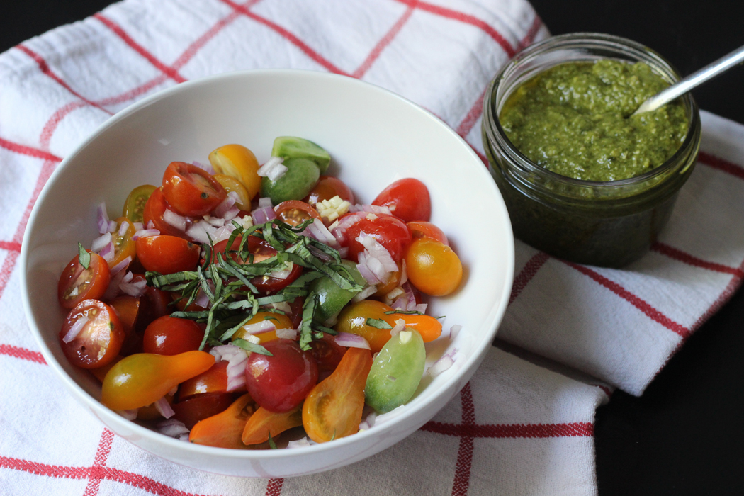 a bowl of heirloom grape tomatoes with basil and red onion with a small bowl of pesto