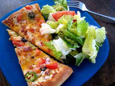 A slice of pizza on a blue plate, with Salad