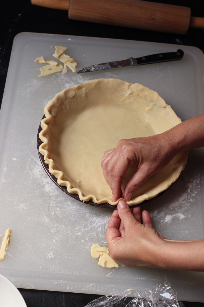 hands crimping pie crust in pan