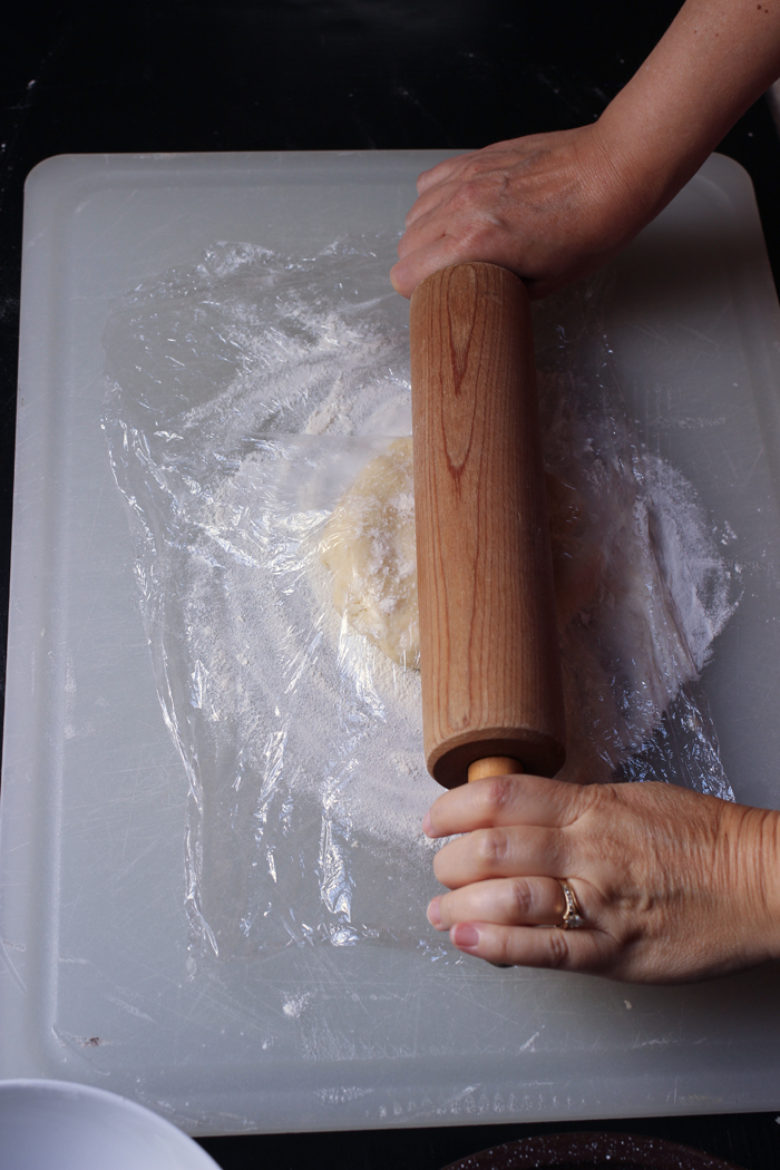 rolling out pie crust with plastic wrap and rolling pin