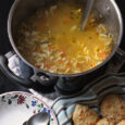 pot of Chicken Noodle Soup with bowls and biscuits
