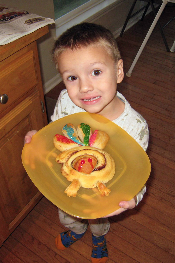 boy holiding plate with cinnamon roll turkey