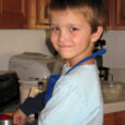 boy in blue apron cooking in kitchen