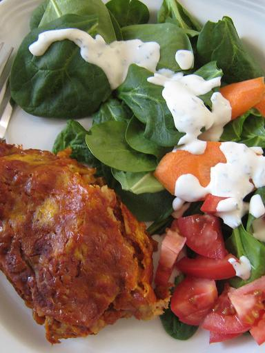 A close up of a plate of Enchilada and salad