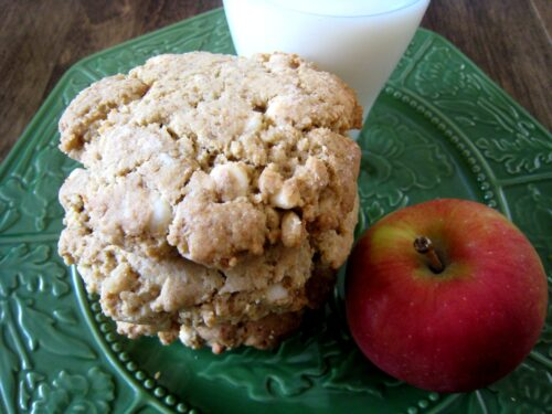 White chocolate chip cookies stacked on a plate with an apple