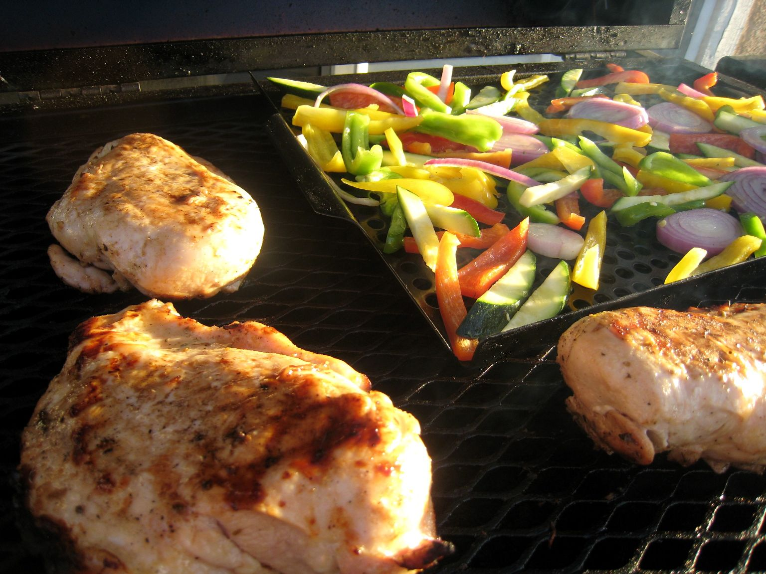 A close up of chicken and vegetables on a grill