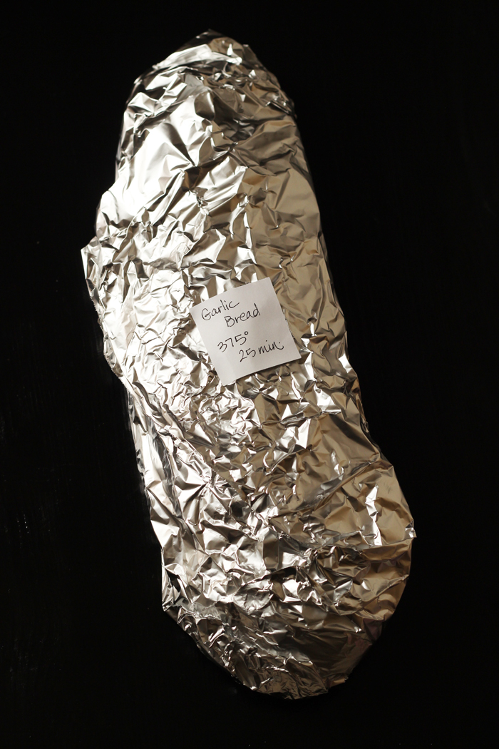 garlic bread wrapped up in aluminum foil with a post-it with directions on it