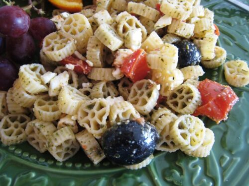 A pasta salad with roasted tomatoes and pesto