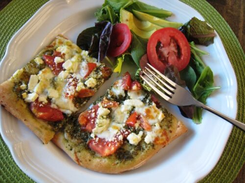 feta pesto pizza slices on a plate with salad