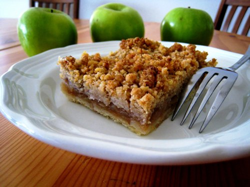 A plate of apple pie with fork and apples