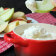 red dish of maple whipped cream with apple slice dipped