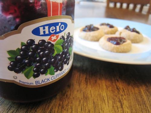 close up of jam jar next to plate of thumbprint cookies