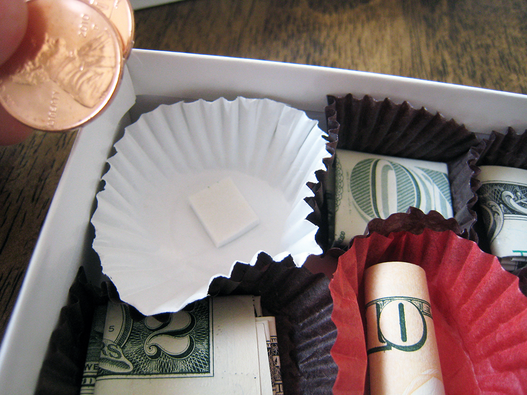 hand putting a penny in chocolate box of money