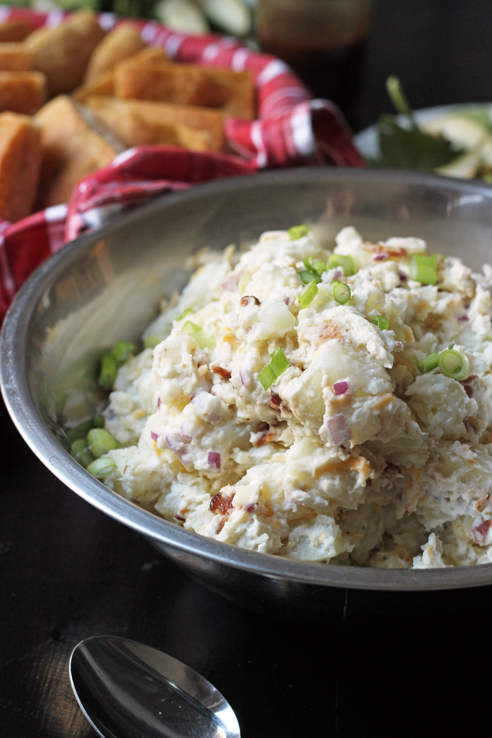 bowl of loaded potato salad with bread basket
