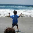 boy at beach raised arms