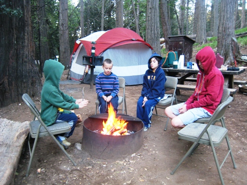 A group of kids sitting by a fire