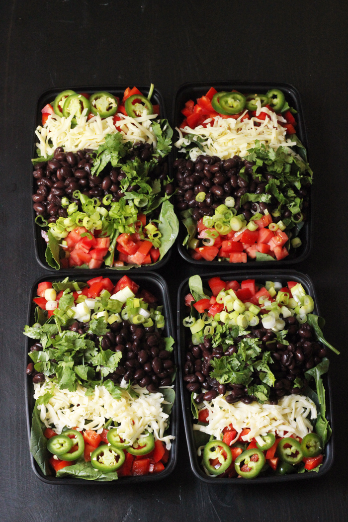 black to go trays with black bean taco salads