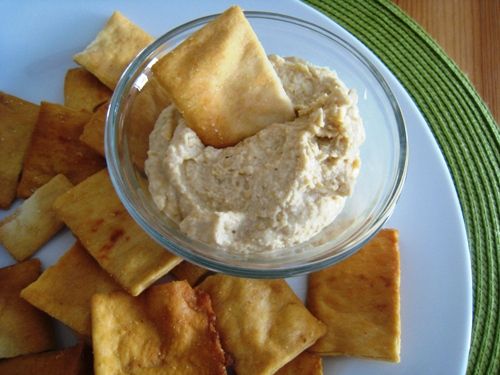 a bowl of hummus on a plate of chips