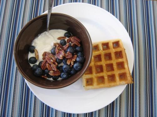 A zucchini waffle on a plate with bowl of yogurt
