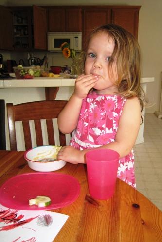 A little girl licking hummus off her hand