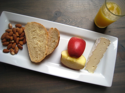 A tray of apples, cheese, bread, and nuts