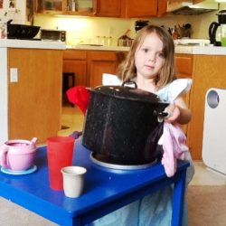 little girl canning in her kitchen