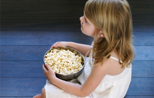 A little girl holding a bowl of popcorn