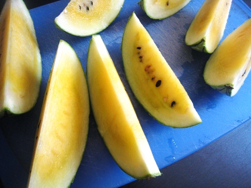 wedges of yellow melon on blue cutting board