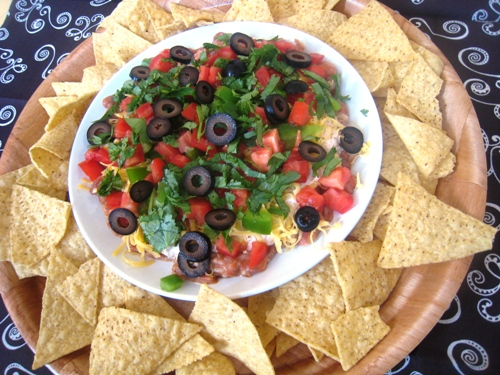 seven layer dip surrounded by tortilla chips