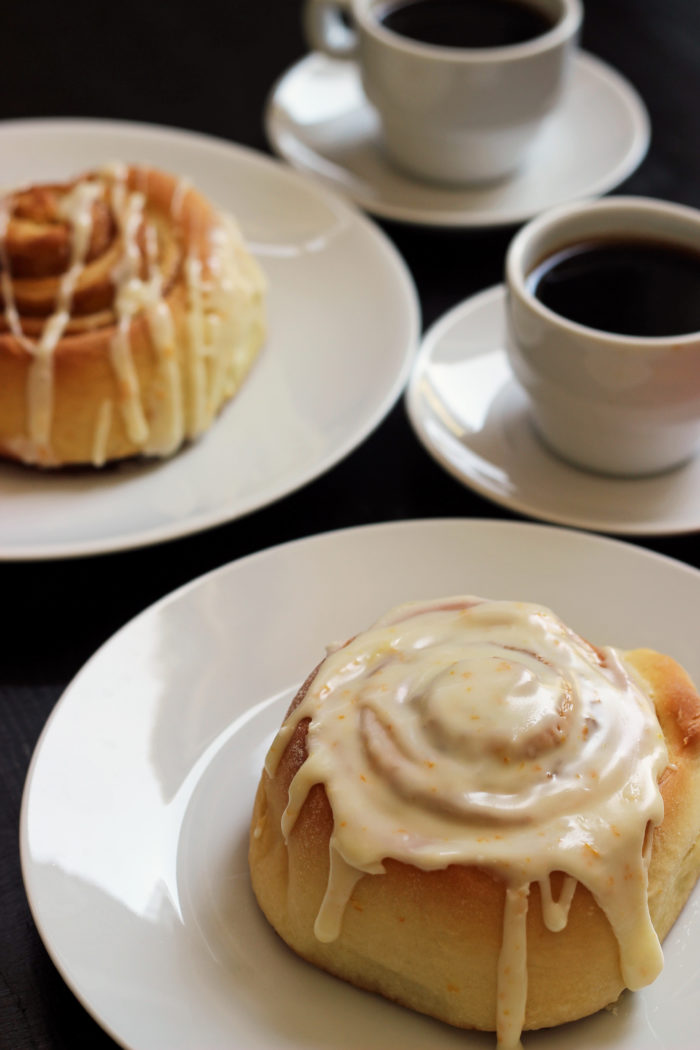 two glazed orange sweet rolls and two cups of espresso